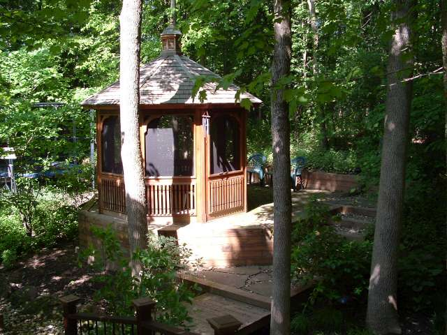 Elevated gazebo in wooded area with stream in background.