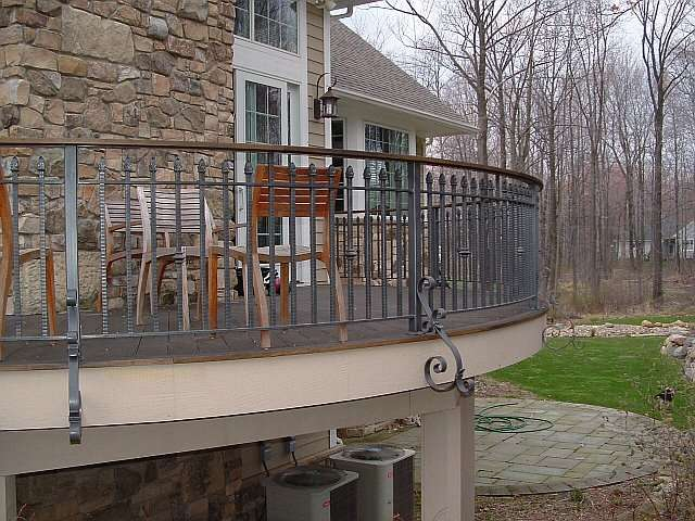 Outdoor iron railing surrounds an elevated stone and brick patio in this landscape design.