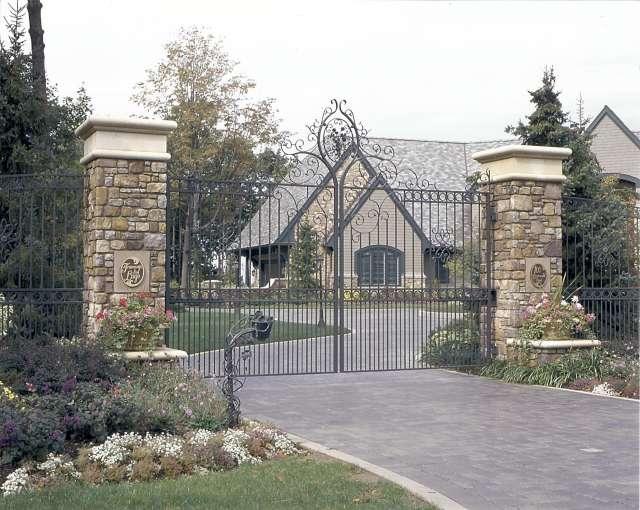 Custom Iron Gate At Main Entrance Set Between Large Stone Pillars Designed By Landscape Architect