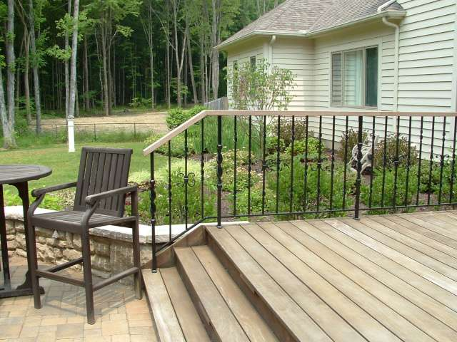 Custom iron rail at backside of deck leading to brick patio with stone wall and landscape plantings in the backround.