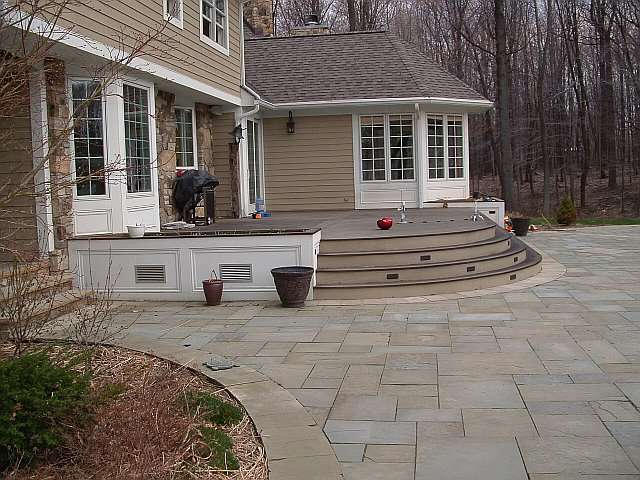 A Landscape Architect designed this large stonework patio which surrounds an elevated outdoor deck.