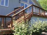 Custom woodwork and ironwork railing border a set of steps that join two deck levels as part of this landscape design.