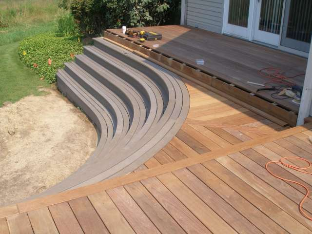 Outdoor deck with step down and circular treaded stairs complement this backyard landscape design.