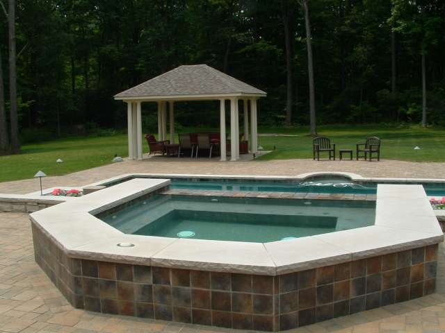 Landscape design showing brick patio and outdoor spa with pool and pavillion in background.