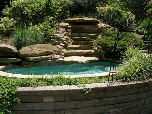 Custom landscape design, natural stone outdoor spa with waterfall. Spa is set inside landscaped bed surrounded by stone retaining wall