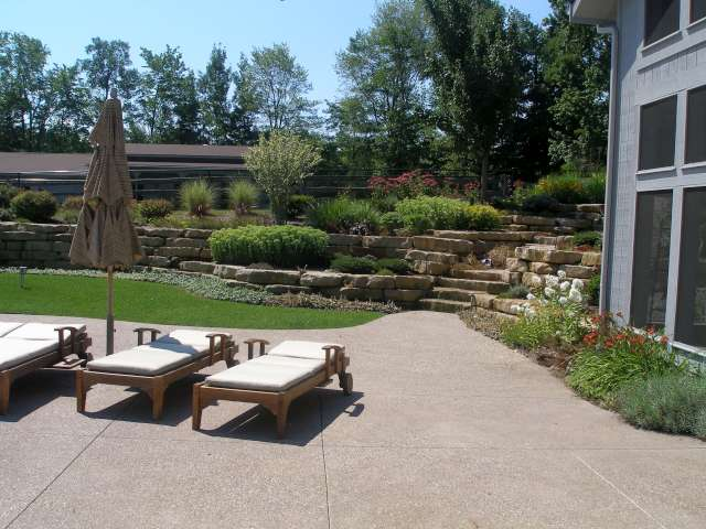 Solon Ohio home showing patio and hillside landscape designed with natural stone retaining walls