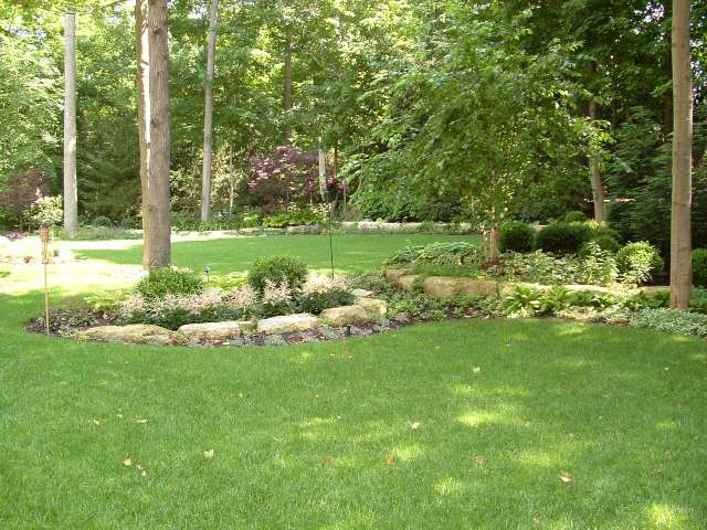 Backyard landscape design with natural stone planters filled with a variety of woodland plantings.